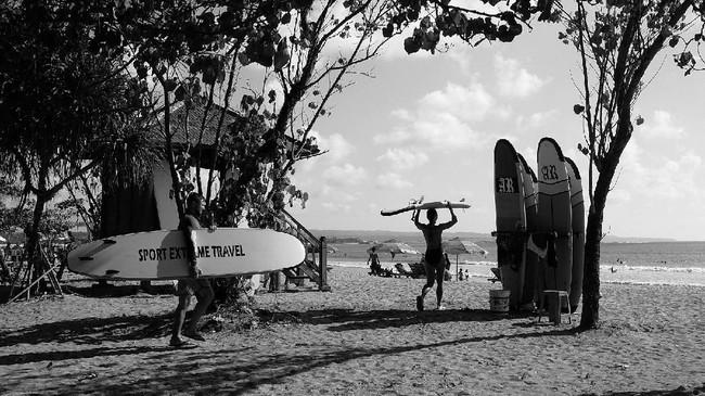 Peselancar merupakan obyek yang banyak ditemukan di Pantai Kuta. Scholastika Mariani berhati-hati memilih angle dan posisi jatuhnya cahaya untuk rekaman fotonya. Ia memilih aspek gestur pada obyek yang difoto. Elemen pohon membentuk framing pada dua obyek peselancar.