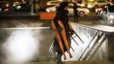 Seorang perempuan membawa separuh manekin keluar dari terminal bawah tanah di Moskow, Rusia. (Photo by Mladen ANTONOV / AFP)