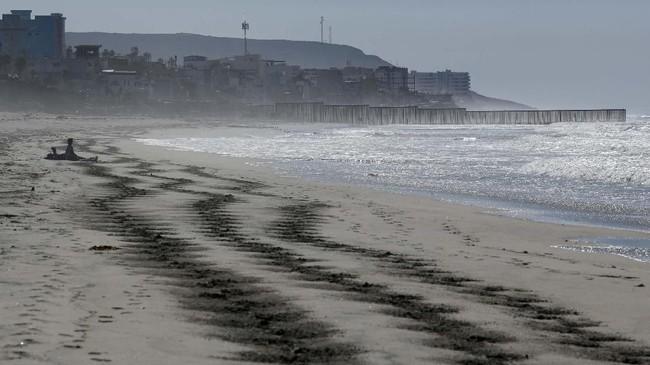Sepasang kekasih migran duduk di tepi pantai di San Diego, pantai yang juga menjadi perbatasan Amerika Serikat dan Meksiko. (REUTERS/Mike Blake)