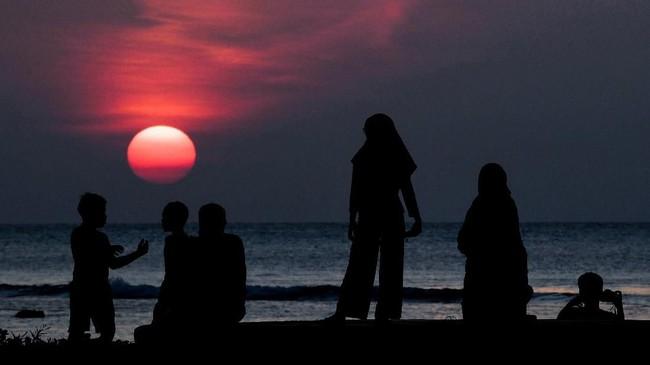 Pengunjung menyaksikan matahari tenggelam di kawasan KEK Tanjung Lesung, Pandeglang, Banten.