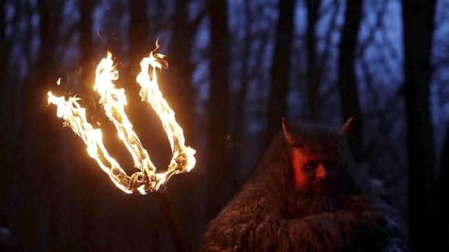Seorang pria yang mengenakan kostum setan berdiri di depan gua pasir di sebuah desa di Svitava, dekat kota Cvikov, Republik Ceko. (REUTERS/David W Cerny)