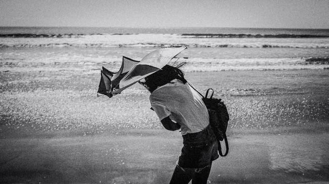 Momen merupakan bagian dari aspek fotografi jalanan. Kesigapan merekam obyek foto memang diperlukan ditambah penguasaan kamera yang digunakan. Pande Parwata berhasil merekam momen fotografi jalanan dari seorang pengunjung yang mencoba mempertahankan payungnya dari terpaan angin pantai.
