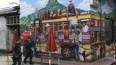 Dua orang polisi berjalan melewati sebuah gambar mural. Penyelenggara menyatakan Mural Festival diselenggarakan untuk mengubah pandangan negatif terkait San Carlos. (Photo by JOAQUIN SARMIENTO / AFP)