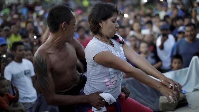 Di tengah ketidakpastian dan harapan, pasangan ini menyempatkan diri menari untuk bersantai sejenak di kamp migran di Meksiko. (REUTERS/Ueslei Marcelino)