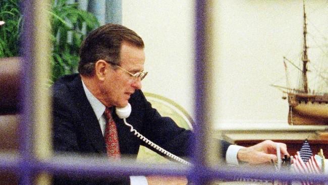 Presiden George H. W. Bush bekerja di Gedung Putih saat serangan Operasi Badai Gurun terus berlangsung. Bush mengirim sedikitnya 425 ribu tentara ke Kuwait demi membendung Irak dibantu sekitar 118 ribu pasukan Perserikatan Bangsa-Bangsa (PBB) dan sekutu. (Photo by J. DAVID AKE / AFP)