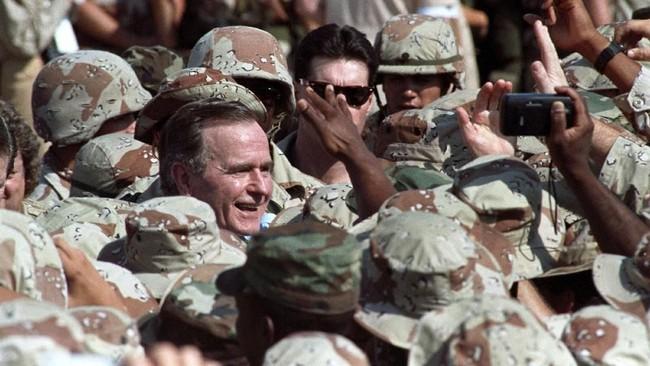 Presiden George H. W. Bush dikelilingi prajurit AS saat seremoni penyambutan di kota Dhahran, Arab Saudi. Selama periode 1989-1993, Bush menerapkan sejumlah kebijakan luar negeri yang didominasi pendekatan militer. (REUTERS/Terry Bochatey)