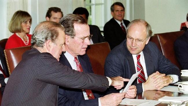 Presiden George H.W. Bush mendiskusikan Perang Teluk di salah satu ruangan Gedung Putih, Washington, dengan Menteri Pertahanan Dick Chaney dan Menteri Luar Negeri James Baker. Bush dikenal sebagai presiden yang sukses dengan politik luar negerinya. (Photo by J. DAVID AKE / AFP)