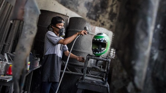 Pekerja menyelesaikan proses pengecatan helm kustom di Solo, Jawa Tengah. (ANTARA FOTO/Mohammad Ayudha)