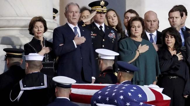 Jenazah yang dibawa menggunakan peti berlapis bendera AS itu tiba di ruang Rotunda pada Senin sore. Para anggota kabinet Bush menyambut dengan meletakkan tangan di dada, tanda hormat pada sang presiden ke-41 itu. (Alex Brandon/Pool via Reuters)