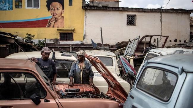 Elyse Rakotondrakonona (sebelah kanan) bersama seseorang berdiri di depan Renault 4L di bengkelnya yang berlokasi di Antananadikina, Antananarivo. (Photo by MARCO LONGARI / AFP)