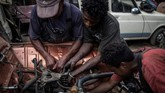 Mekanika muda bekerja sedang memperbaiki mesin Renault 4L di bengkel Elyse Rakotondrakonona di Antamoadikina, Antananarivo. (Photo by MARCO LONGARI / AFP)