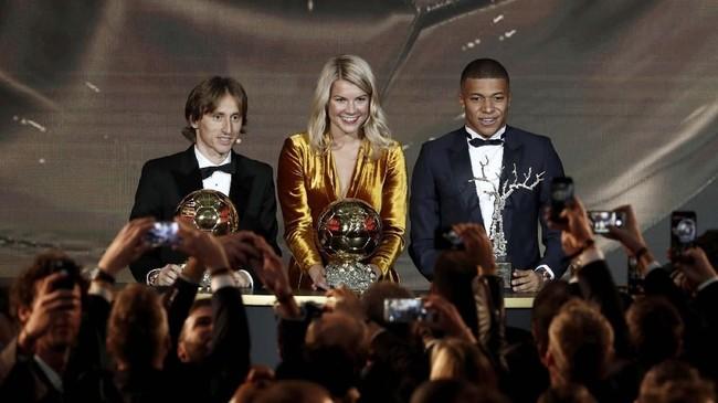 Penyerang Real Madrid Luka Modric, penyerang Olympique Lyonnais Ada Hegerbergdan penyerang PSG Kylian Mbappe di atas podium sebagai penerima pengargaan di acara Ballon d'Or. (REUTERS/Benoit Tessier)