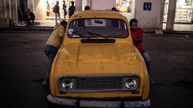 Warga setempat sedang mendorong mobil klasik Renault 4L yang ditemui di ibu kota Madagaskar, Antananarivo. Mobil Prancis yang ikonik ini produksi antara 1961 hingga 1994 di Slovenia.(Photo by MARCO LONGARI / AFP)