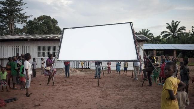 Anak-anak Afrika untuk pertama kalinya dalam hidup melihat layar lebar yang akan digunakan menonton film bersama. Mereka berkerumun dan menunggu dengan tak sabar. (Photo by FLORENT VERGNES / AFP)