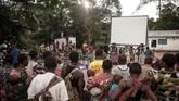 Penduduk lokal dari kaum Pygmy berkumpul bersama di dekat Bayanga, sembari menunggu pemutaran film di bioskop berjalan. (Photo by FLORENT VERGNES / AFP)