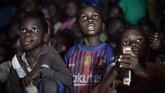 Ketika melihat mobil saja sudah menjadi pengalaman baru untuk mereka, inilah sebagian ekspresi anak-anak Afrika ketika menonton film di bioskop berjalan. (Photo by FLORENT VERGNES / AFP)
