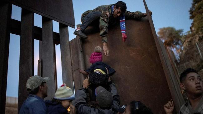 Sejumlah imigran dari Honduras berusaha menerobos pagar perbatasan antara Amerika Serikat dan Meksiko. (REUTERS/Alkis Konstantinidis TPX IMAGES OF THE DAY)