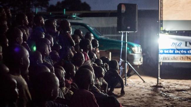 Bocah-bocah Afrika bersemangat menonton film di layar lebar, menjadi pengalaman pertama yang mengesankan. (Photo by FLORENT VERGNES / AFP)