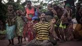 Kaum Pygmy di kawasan Mbyaka, Afrika, menari-nari kegirangan menyambut datangnya bioskop berjalan di desa mereka. (Photo by FLORENT VERGNES / AFP)