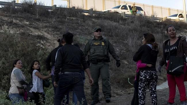 Sejumlah imigran sempat berhasil menerobos pagar perbatasan di Meksiko, tetapi kemudian ditangkap penjaga perbatasan AS. (REUTERS/Alkis Konstantinidis)
