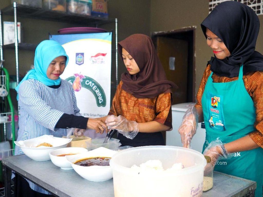 Pemilik Bu Kus Catering, Wagini (kiri) mengawasi proses pembuatan makanan di dapur sementara yang dibangun pascagempa. Walaupun sempat terganggu operasionalnya, Wagini tetap dapat melayani permintaan pelanggan, salah satunya, rombongan Presiden Republik Indonesia yang datang ke Mataram pada November lalu. Pool/YDBA.