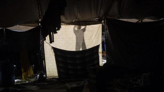 Setelah hujan deras usai, bayangan seorang imigran yang berjalan selama sebulan penuh melintasi Amerika Tengah dan Meksiko dengan menggunakan karavan, terlihat di sebuah penampungan sementara di Tijuana, Baja California, dekat dengan perbatasan Amerika Serikat. (Photo by Pedro PARDO / AFP)