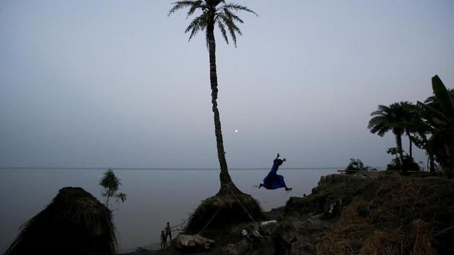 Seorang perempuan bermain di pinggiran pantai Pulau Ghoramara, India. Menurut para tetua, penduduk pulau yang merupakan bagian dari delta Sudarbans di Teluk Bengal itu jumlahnya telah menyusut hingga separuh. (REUTERS/Rupak De Chowdhuri)