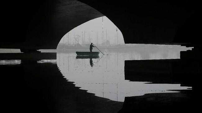Di suatu hari yang berkabut, seorang pria mengayuh perahu setelah peringatan akan datangnya kabut dibunyikan di Provinsi Jiangsu, China. (REUTERS/Stringer)