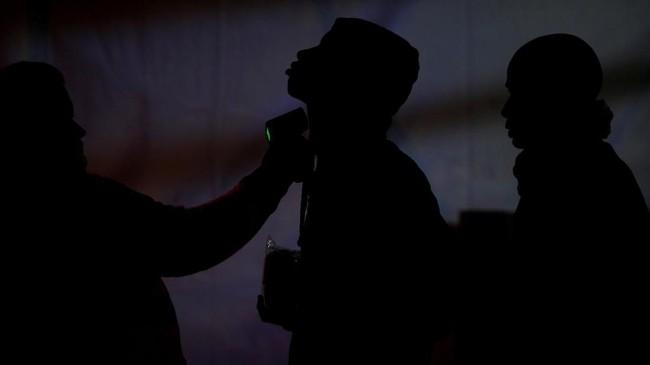 Seorang anggota Palang Merah Spanyol menggunakan termometer untuk memeriksa suhu seorang imigran. Pengungsi itu disetop di tepi laut Mediterania setelah tiba di pelabuhan Malaga, Spanyol bagian selatan, menggunakan perahu. (REUTERS/Jon Nazca)
