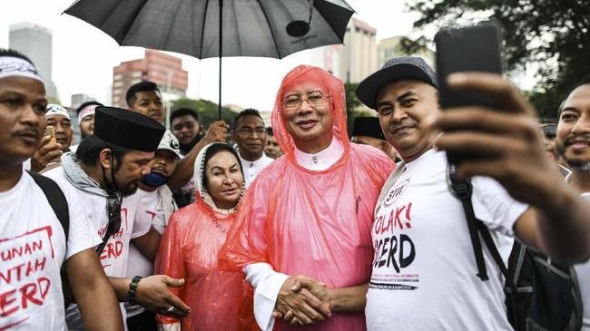 Mantan Perdana Menteri Malaysia, Najib Tun Razak, beserta sang istri, Rosmah Mansor, turut menghadiri aksi unjuk rasa 812. (Photo by Mohd RASFAN / AFP)
