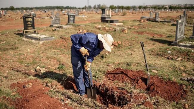 Para penggali kubur di Afrika Selatan terpaksa membongkar liang lahad di salah satu pemakaman di Johannesberg karena mereka sudah kekurangan lahan. (AFP Photo/Gianluigi Guercia)