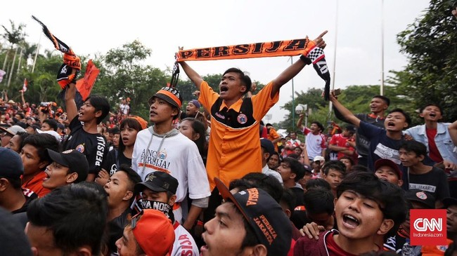 Suporter Persija Jakarta yang tidak kedapatan tiket turut menyaksikan tim kesayangannya berlaga melalui layar besar di sekitar Senayan, Jakarta. (CNN Indonesia/Hesti Rika)