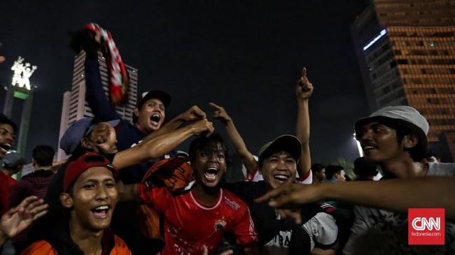 Wajah-wajah ceria terpancar di setiap wajah suporter yang larut dalam perayaan juara Persija Jakarta yang sudah dinantikan selama 17 tahun terakhir. (CNN Indonesia/Hesti Rika)