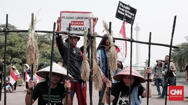 Teatrikal di balik jeruji oleh para aktivis Walhi untuk menyampaikan kritik atas para pejuang lingkungan hidup yang dituding sebagai pelaku kriminal. (CNN Indonesia/Andry Novelino)