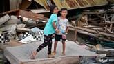 Zidan (kanan) dan Caca berpose di depan rumahnya yang rusak akibat gempa dan tsunami di Wani, Donggala, Sulawesi Tengah. BNPB mencatat penghitungan kerugian per 27 Oktober 2018 akibat gempa palu mencapaisekitar Rp18,4 triliun. (ANTARA FOTO/Wahyu Putro A)