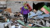 Lina berpose di depan rumahnya yang rusak akibat gempa dan tsunami di Lere, Palu, Sulawesi Tengah. Wapres RI Jusuf Kalla menyatakan proses rekontruksi di Palu akan fokus pada relokasi warga dan dimulai pada Januari 2019. (ANTARA FOTO/Wahyu Putro A)