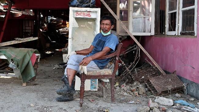 Abdullah H Terra berpose di depan rumahnya yang rusak akibat gempa dan tsunami di Wani, Donggala, Sulawesi Tengah. Akibat gempa dantsunami di wilayah itu sebanyak 17 ribu rumah warga rusak. (ANTARA FOTO/Wahyu Putro A)