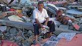 Sukur Sultan membawa foto keluarga yang meninggal akibat gempa dan tsunami di Wani, Donggala, Sulawesi Tengah. Pada 28 September 2018, gempa berkekuatan 7,4 SR mengguncang wilayah itu disusul tsunami dan peristiwa likuifaksi. Sutan kehilangan ibu, anak, dan cucunya akibat tusnami. (ANTARA FOTO/Wahyu Putro A)