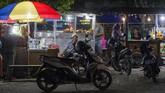 Pedagang kaki lima kembali berjualan di salah satu ruas jalan. Tak seperti ketika bencana hadir, satu-satunya penanda kehidupan adalah perbukitan yang sesak oleh warga diliputi ketakutan. (ANTARA FOTO/Basri Marzuki).