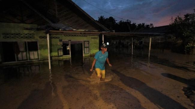 Warga memeriksa rumahnya yang terendam banjir di Desa Dungaliyo, Kabupaten Gorontalo, Gorontalo, Minggu (9/12). Banjir setinggi dua meter kiriman air dari daerah pegunungan tersebut menerjang puluhan rumah di daerah itu. (ANTARA FOTO/Adiwinata Solihin/ama).