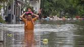 Seorang warga melintasi banjir saat mengevakuasi keluarganya di kawasan perumahan jalan Pura Demak, Denpasar, Sabtu (8/12). Hujan deras yang mengguyur wilayah Bali selatan pada Sabtu dinihari menyebabkan sejumlah kawasan di Denpasar terendam banjir sehingga sejumlah warga dievakuasi. (ANTARA FOTO/Adhi Prayitno/nym/hp).