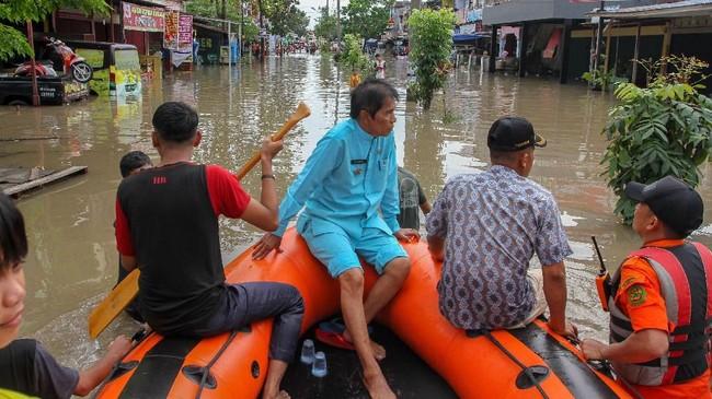 Petugas Basarnas menggunakan perahu karet saat mengevakuasi warga dari rumahnya yang terendam banjir di Perumahan Sidomulyo, Kota Pekanbaru, Riau, Selasa (11/12). Tingginya curah hujan membuat sejumlah kawasan terendam banjir dan merendam ratusan rumah warga dengan ketinggian air 30 cm - 150 cm. (ANTARA FOTO/Rony Muharrman)