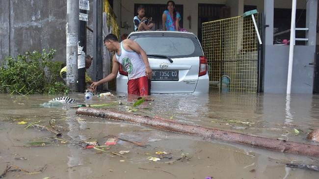 Seorang warga membersihkan sampah yang terbawa banjir di kawasan perumahan jalan Pura Demak, Denpasar, Sabtu (8/12). Hujan deras yang mengguyur wilayah Bali selatan pada Sabtu dini hari menyebabkan sejumlah kawasan di Denpasar terendam banjir sehingga sejumlah warga dievakuasi. (ANTARA FOTO/Adhi Prayitno/nym/hp).