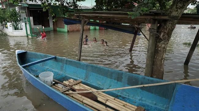 Sejumlahanak bermain di genangan banjir yang merendam permukiman penduduk di Desa Gunungreja, Sidareja, Cilacap, Jawa Tengah, Kamis (6/12). Sebanyak 3.499 KK terdampak banjir yang merendam 13 Desa di Kabupaten Cilacap, akibat hujan deras selama dua hari terakhir. (ANTARA FOTO/Idhad Zakaria/foc)