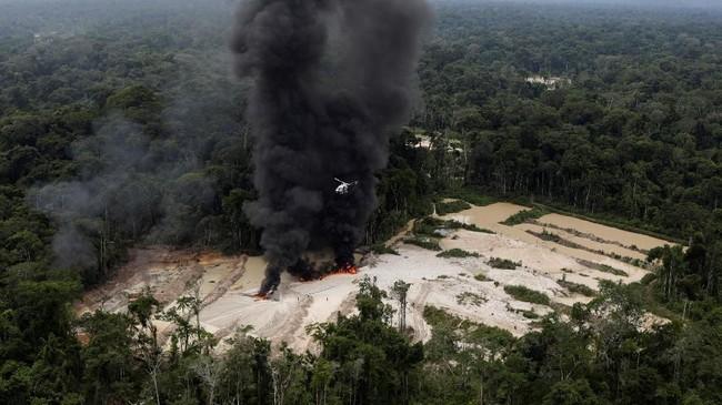 Tak mampu menyita langsung mesin tambang yang ada di lapangan, para agen akhirnya memutuskan untuk membakarnya, membuat asap mengepul di sekitar hutan. (Reuters/Ricardo Moraes)