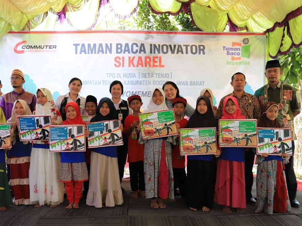 Anak-anak memegang poster aksi cinta KRL saat peresmian Taman Baca Inovator Si Karel di Kampung Sukasari, Desa Tenjo, Kecamatan Tenjo Kabupaten Bogor. Pool/KCI.