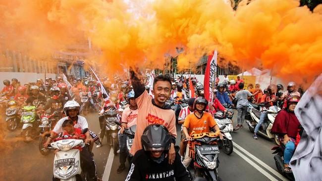 Wajah ceria suporter Persija Jakarta, The Jakmania, menghiasi jalan-jalan jalur konvoi pawai juara Macan Kemayoran yang dimulai dari GBK hingga Balai Kota DKI Jakarta. (ANTARA FOTO/Rivan Awal Lingga)