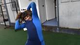 Lopez mengenakan wetsuit-nya sebelum melakukan latihan selancar di Pantai Salinas, Spanyol.