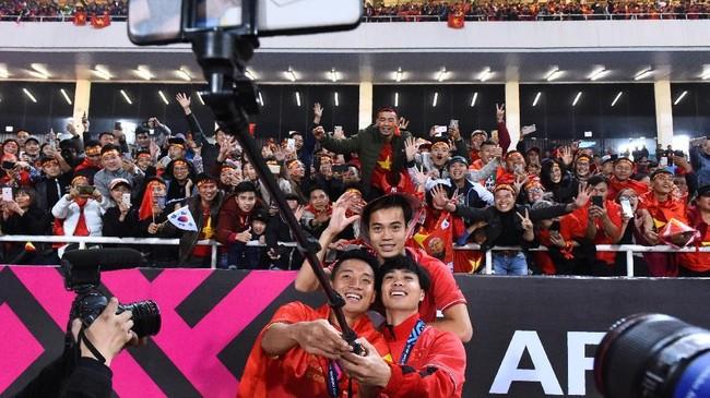 Pemain-pemain timnasplayers berselebrasi dengan berfoto bersama suporter. Piala AFF 2018 adalah gelar kedua dari tiga kesempatan berada di final. Pada 1998 Vietnam gagal juara usai kalah 0-1 dari Singapura. (Photo by Nhac NGUYEN / AFP)