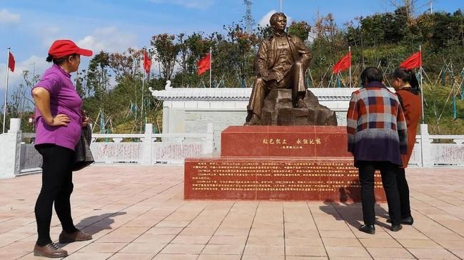 Di jantung desa yang miskin di Shazhou, Rucheng, selatan China, patung tetua China Mao Zedong berdiri. Patung yangdiapit diorama tentara merah dan rumah batu bata itu menarik minat wisatawan datang untuk berfoto.(REUTERS/Shu Zhang).